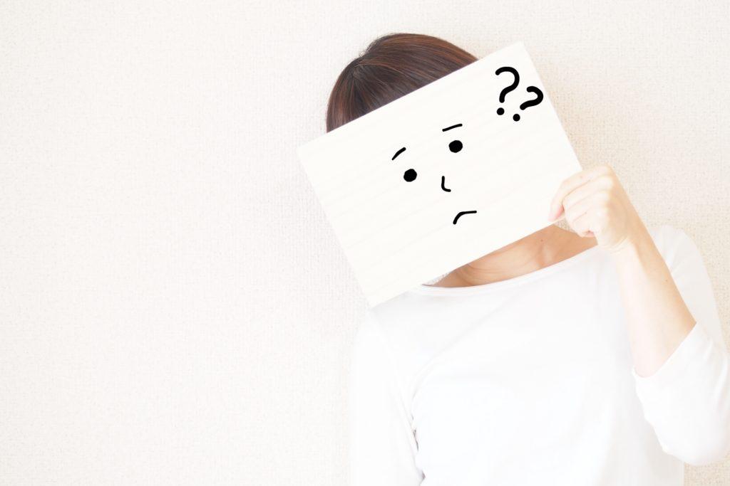 女の人が紙のお面で疑問を浮かべている写真